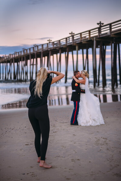 photographer taking picture of bride and groom kissing on beach