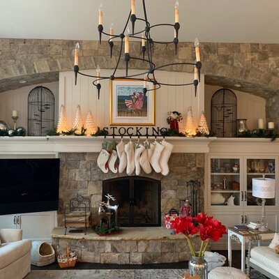 Stone fireplace in living room with chandelier