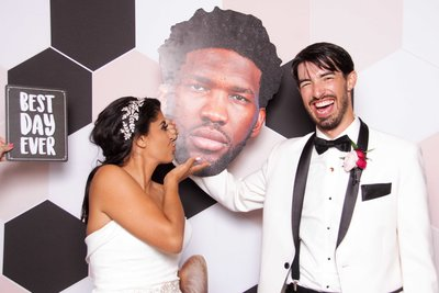 bride kissing a custom prop of a funny guy while groom is holding it