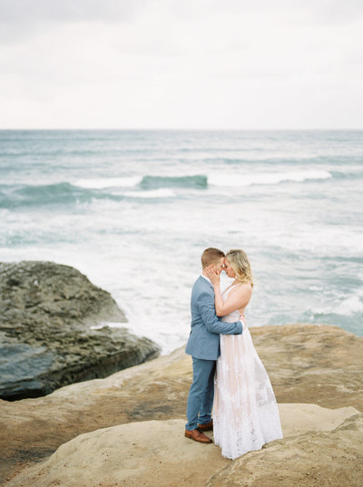 Romantic and refined engagement session with white dress and light blue suit at the Sunset Cliffs in San Diego California by Liz Andolina Photography