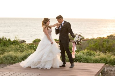 Bride and groom posing on a lookout point over the ocean in Santa Barbara, California