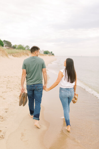 Lexi and Alex walk on the beach in South Haven at their engagement session, photo by Cynthia Boyle, wedding photographer in Michigan