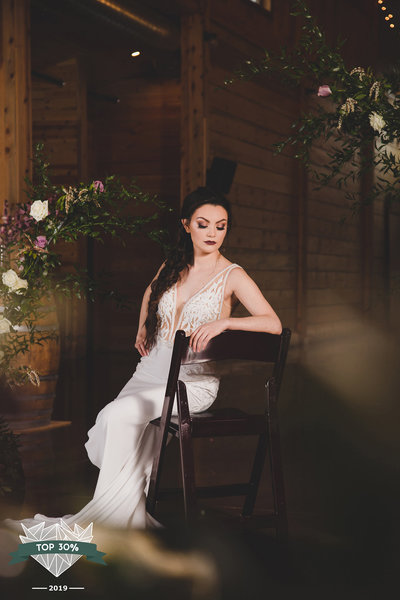 Bride sitting in front of a floral arch