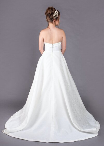 Back view of the Eloise wedding dress with its strapless neckline and textured floral fabric