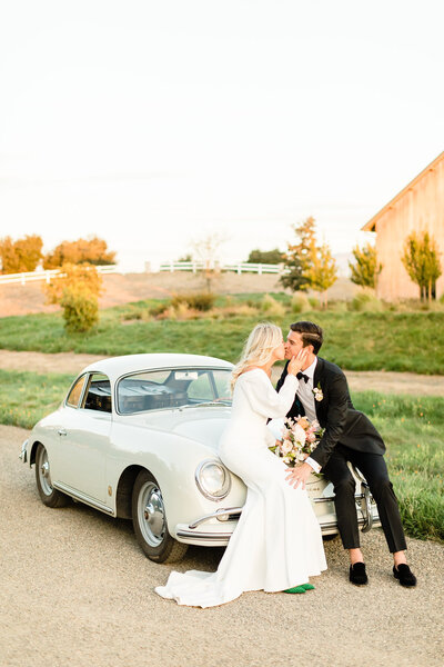 Bride and groom kissing in a vintage car at Brave & Maiden Estate  in Santa Ynez, California. Wedding photo taken by Cheers Babe Photo.