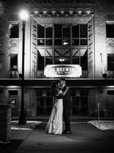 Bride and groom kiss in front of the Brewerie at Union Station at night