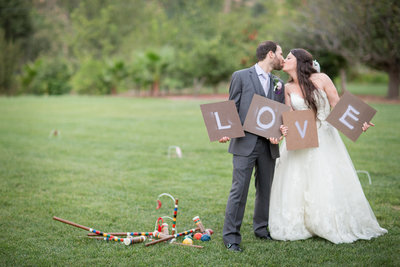 Bride and Groom with Love sign and bocce ball at The Ranch at Bandy Canyon