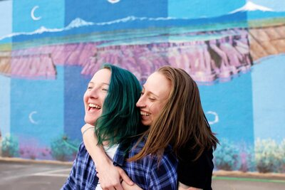 colorful same sex couple laugh and hug in front of bright blue mural