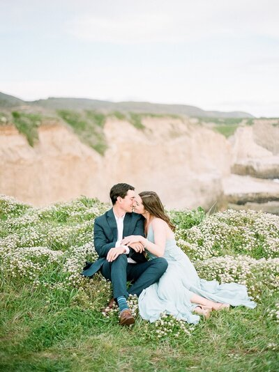 Man and women in blue formalwear sitting in wildflowers on a cliffside in Santa Cruz California for their engagement photos.