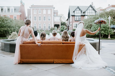 Bridal party sits on orange couch in park.