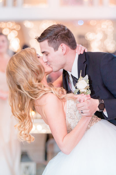 Groom dips bride for a kiss