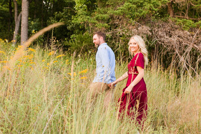 Couple walking in a field in a red dress