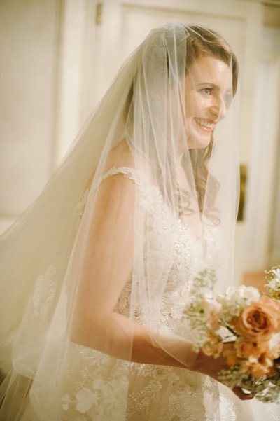 bride wears her veil and holds her bridal bouquet right before walking down the aisle