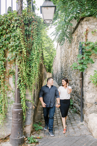 Couple walks ivy covered streets of Paris while holding hands