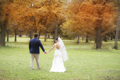 Bride and broom walk through a park with fall colors in the trees