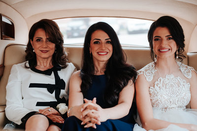Mother of the bride with the bride in a car on wedding day