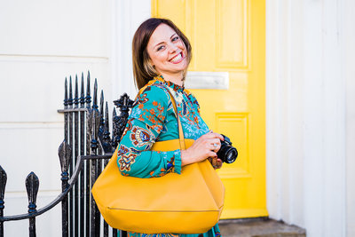 Bio photo of Charlie Flounders holding a yellow bag and her camera, standing in front of a yellow door. She holds her camera to depict that she is a photographer