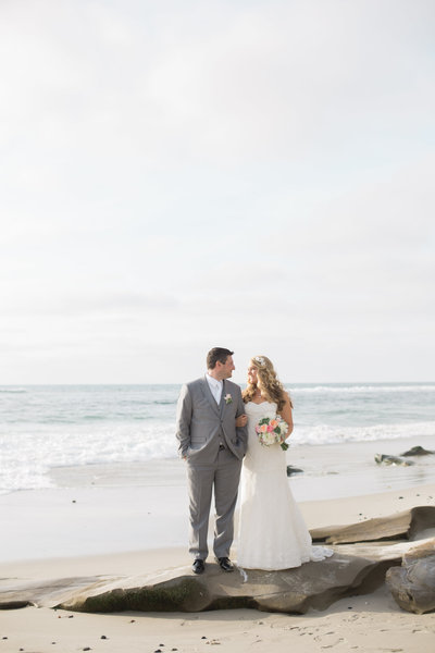 Bride and Groom on rock by ocean at The Darlington House in San Diego