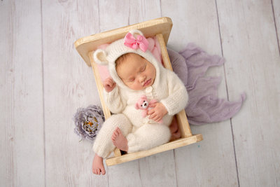 Newborn girl in white teddy bear romper with purple accents