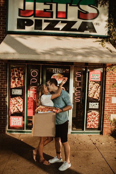 couple kissing in front of pizza shop