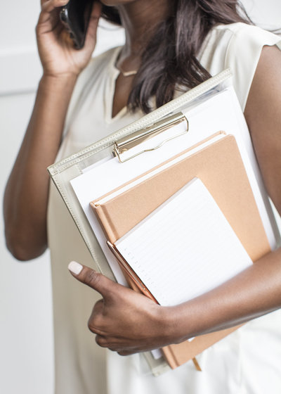woman holding a stack of binders and clipboards