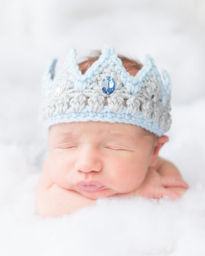 newborn baby boy wearing a blue crochet crown