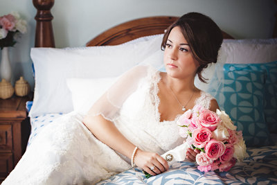Bride lays on bed in Toronto wedding with flowers. The image shows a beautiful bride facing the window with soft light pouring on her dress. The pink flowers contain a bouqet from her grandmother which had significant meaning.