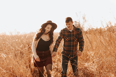 Midwest couple walking through a field holding hands during their fall engagement session