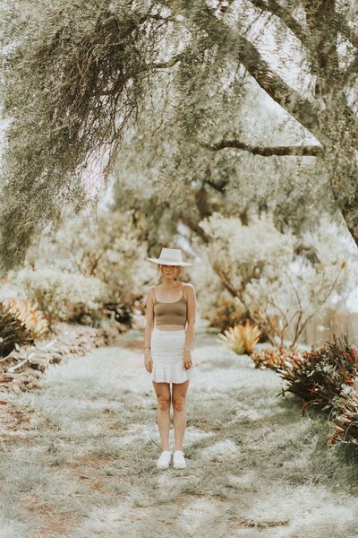 woman wearing a white hat standing under a tree