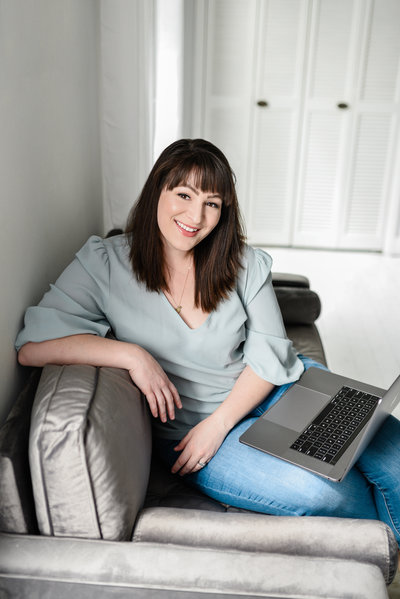 Woman with dark brown hair and bangs sitting on sofa with laptop