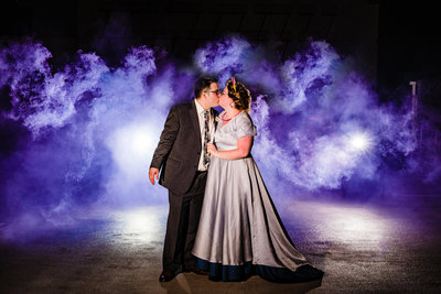 Bride and groom embrace amidst purple smoke