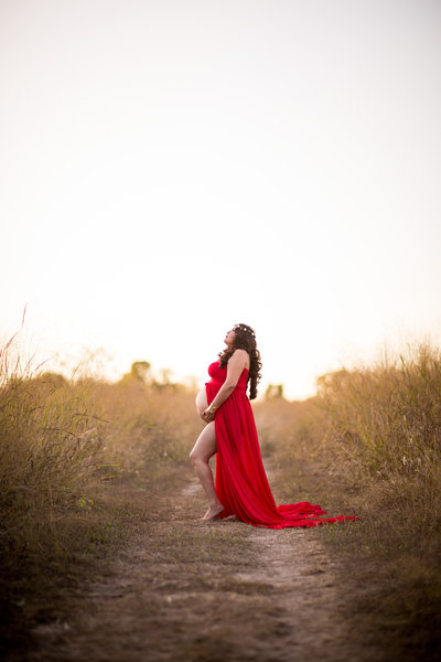 Maternity photo of San Antonio Photographer Irene Castillo standing in a field golden grass at sunset
