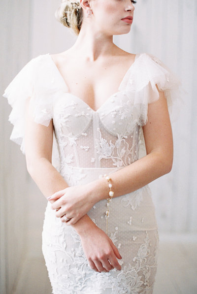 Woman in Berta Bridal gown with sheer lace and fitted bodice grasping her arm