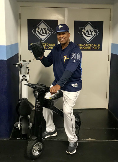 Tampa Bay Rays coach posing on Black Go-Bike M1 with his catcher's mitt