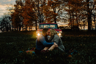 engaged couple kissing in front of old truck with headlights on