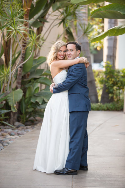 Bride and Groom hugging at their wedding venue at The Dana in San Diego