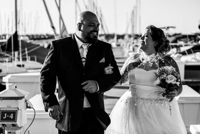 Bride and groom laughing together as they walk the Erie Yacht Club
