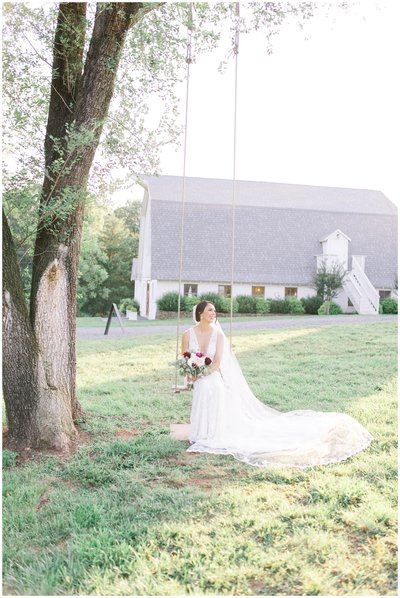 Bride posing on swing with elegant florals at 48 fields. Leesburg Wedding Photographer.