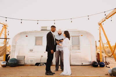 bride and groom getting married in front of an airstream