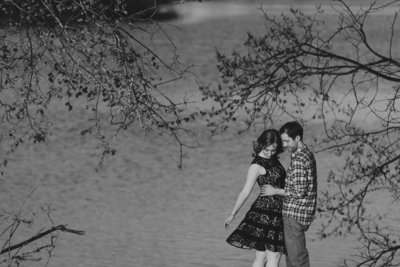 engaged couple among the trees with dress blowing in the wind