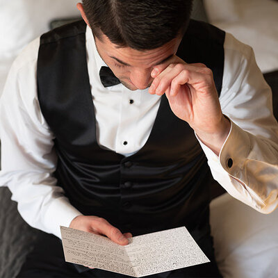 Groom wipes away tear while reading letter from his fiance