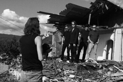 BTS photo black and white photographer Mark Maryanovich directing four members of 5440 standing in front of dilapidated building black and white image