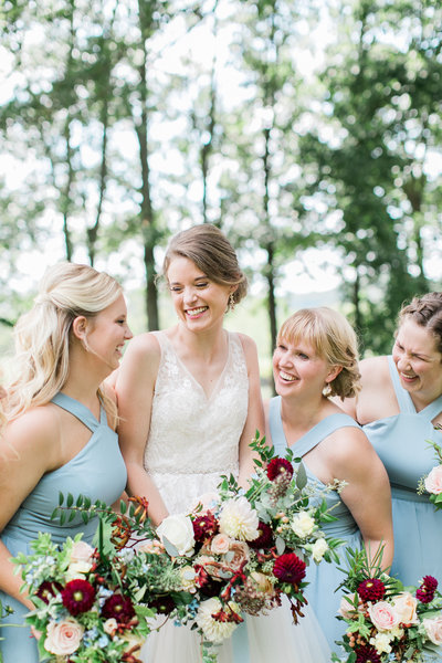 Bride laughs with her bridal party while holding white and burgundy bouquets