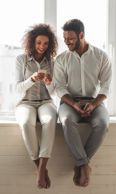 A couple sit on a bench as they smile at something on the woman's phone. This could symbolize a couple searching options for online couples therapy in Florida. Contact a marriage counselor for support with online marriage counseling and other services.