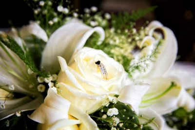 White rose in bridal bouquet with ring. Photo by Ross Photography, Trinidad, W.I..