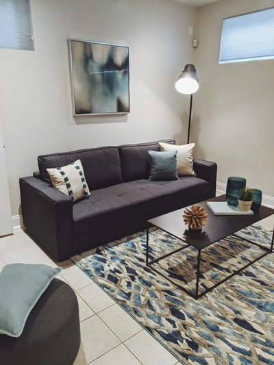HAVEN Home Staging and Redesign - Grenshaw Living Room dark tones dark grey sofa and coffee table blue accessories