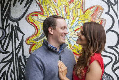 Engaged couple smiling at each other in front of Philadelphia mural