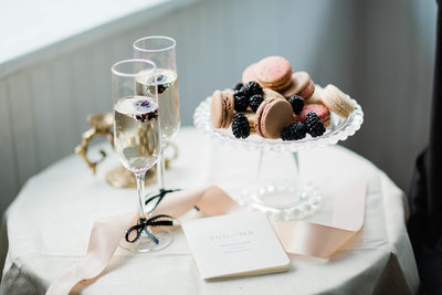 Two champagne flutes with champagne and macarons and blackberries on table adorned with pale pink ribbon