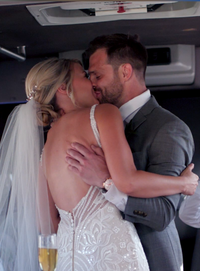 Couple embrace after wedding on party bus