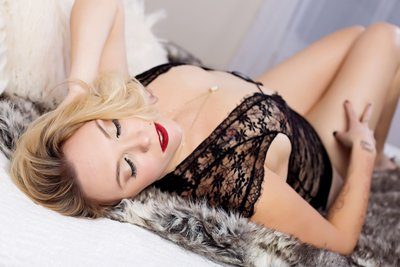 blonde woman laying on her back wearing lingerie on a faux fur rug